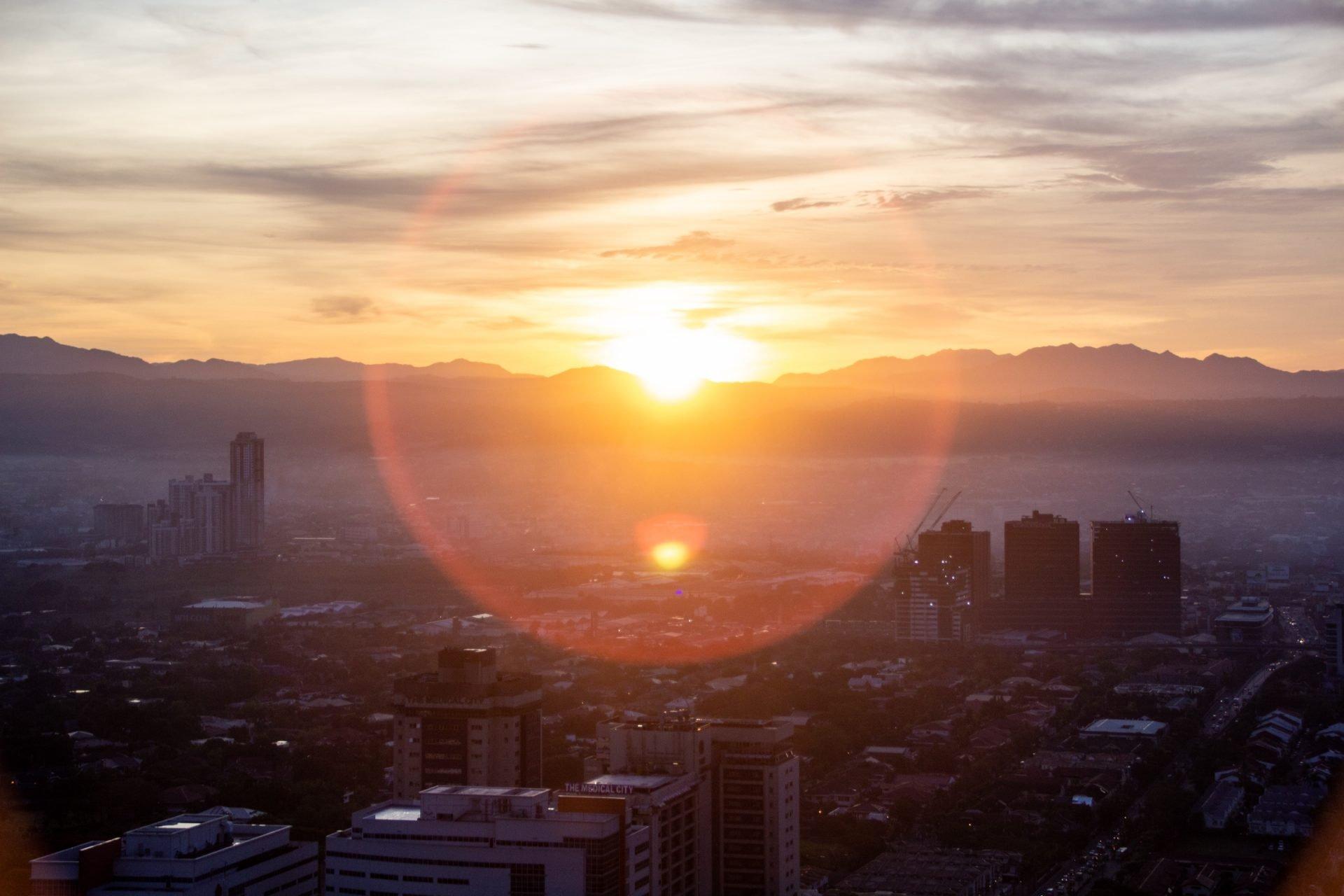 Sun Setting Beyond City