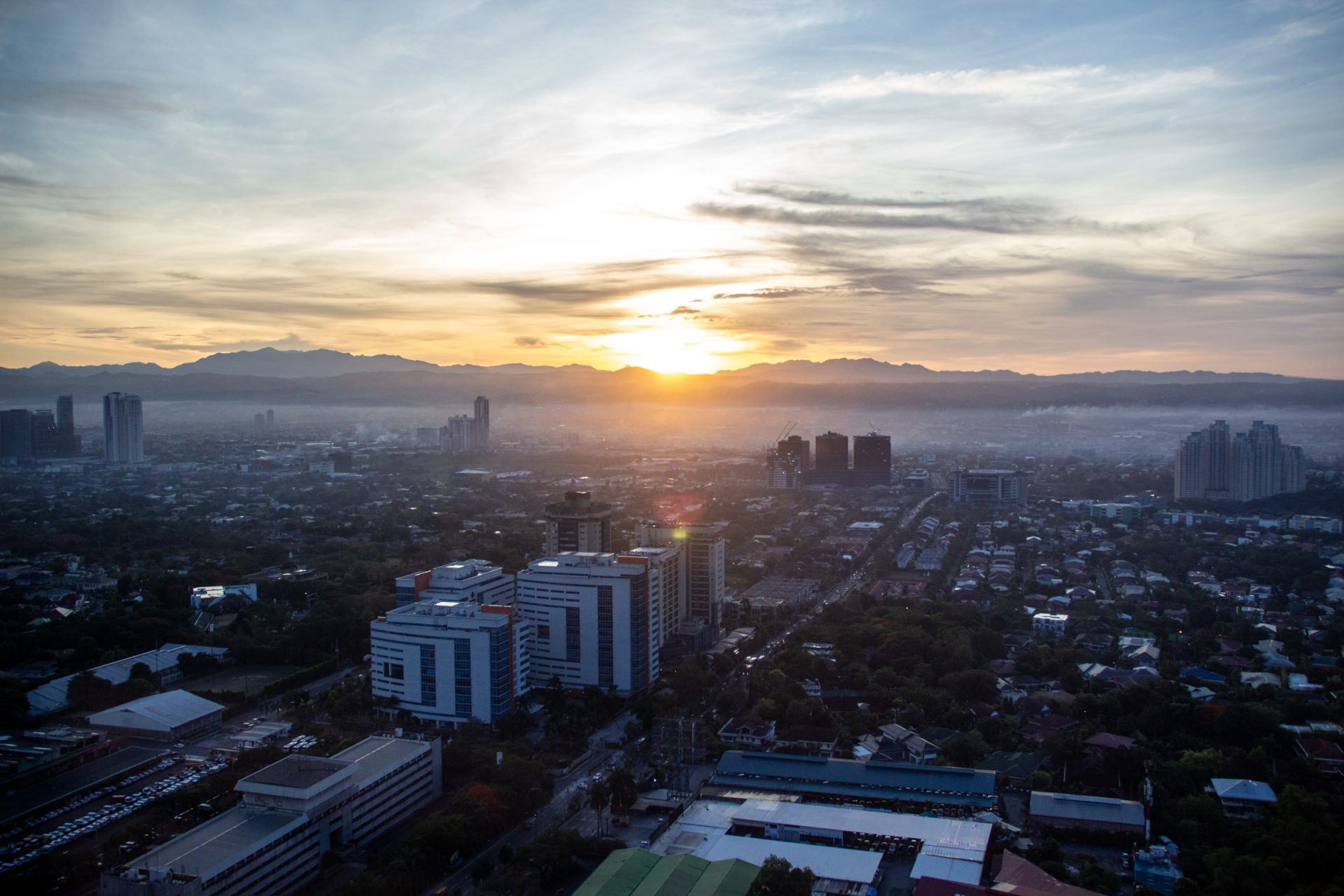 Sun Behind Mountains Beyond Urban Area
