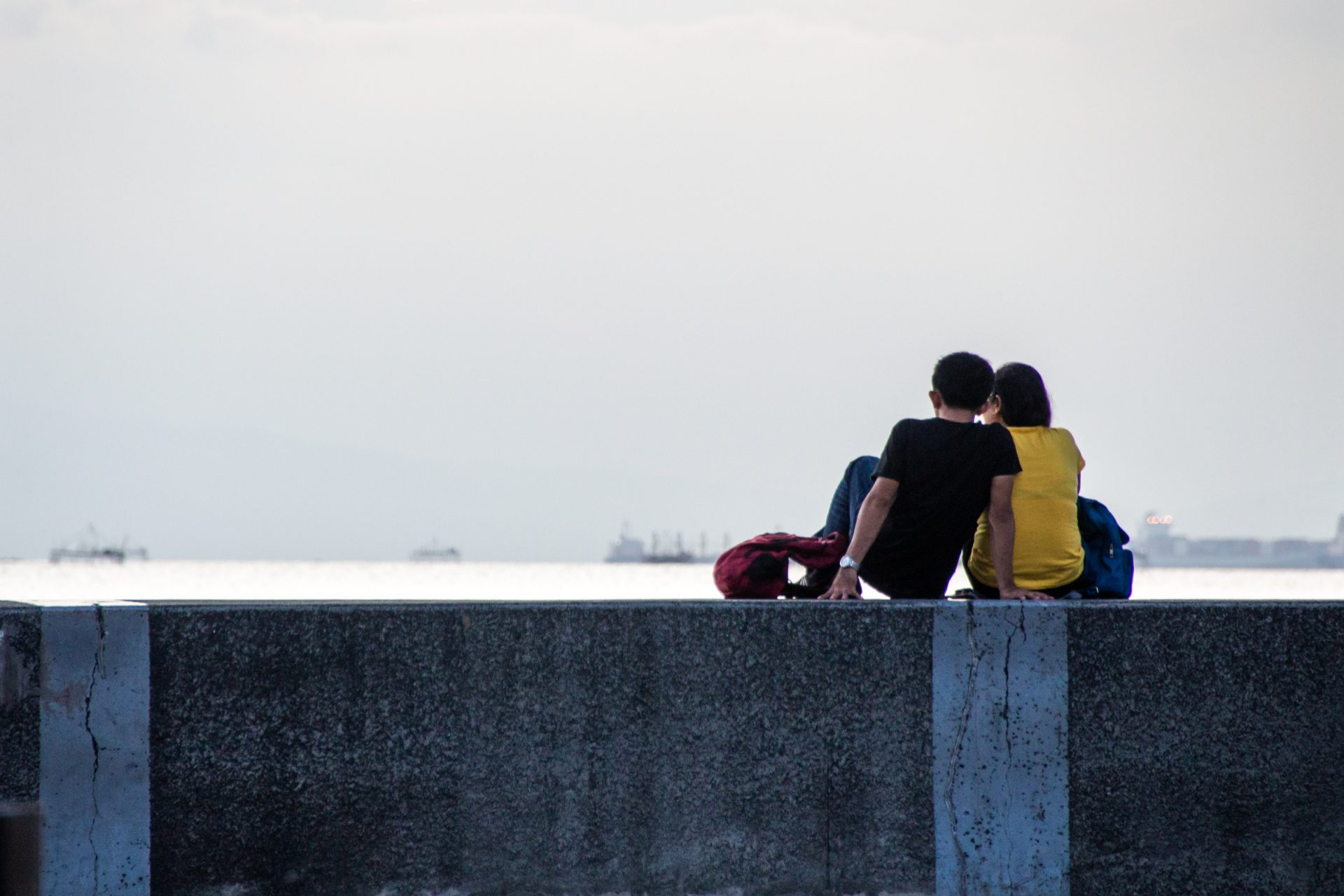 Two People Sitting On Seawall