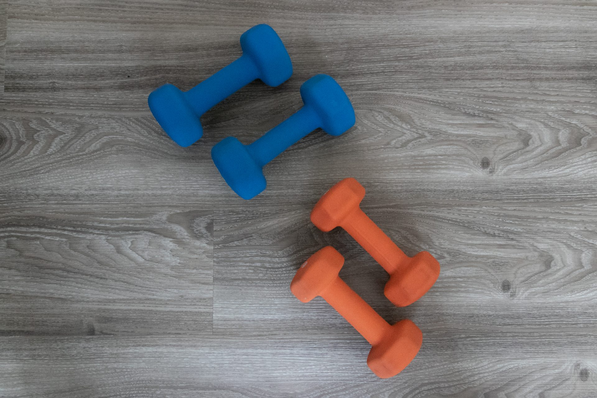Two Sets Of Dumbbells On Wood