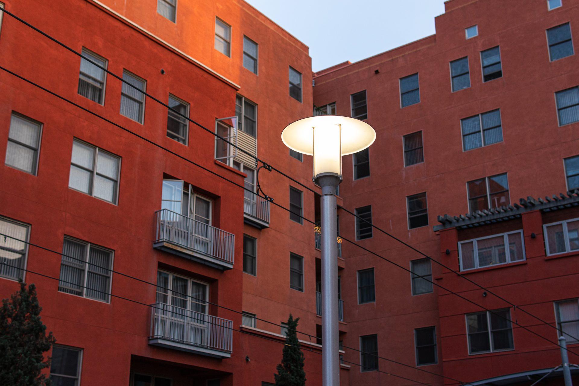 Red Orange Buildings Behind Lit Street Light