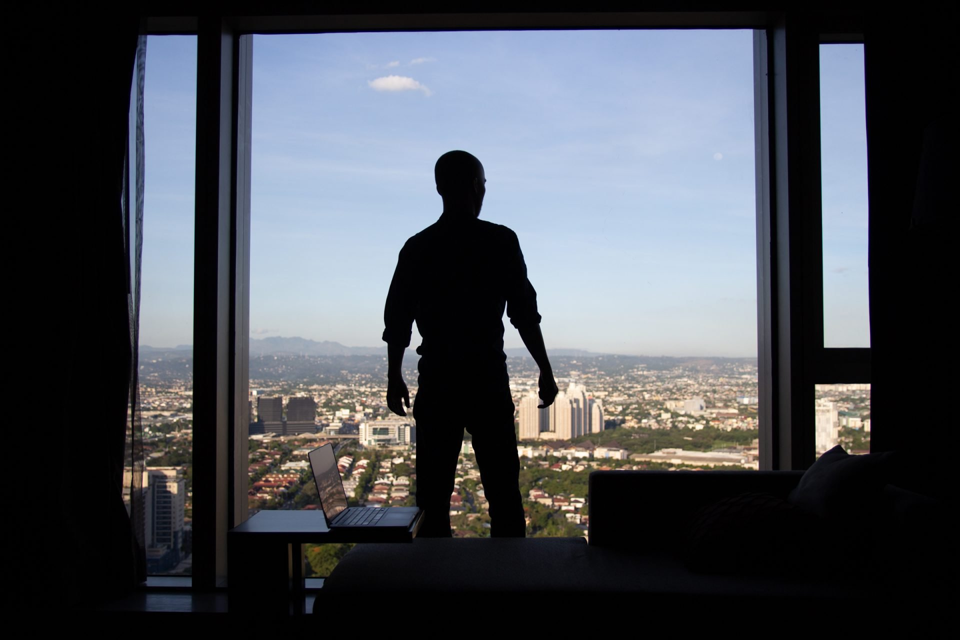 Man In Front Of Window With City View