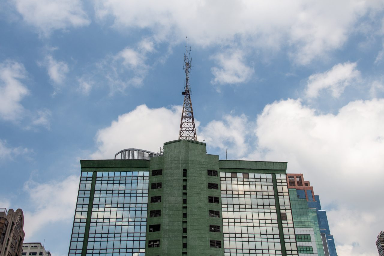 Radio Tower On Building Against White Clouds In Sky