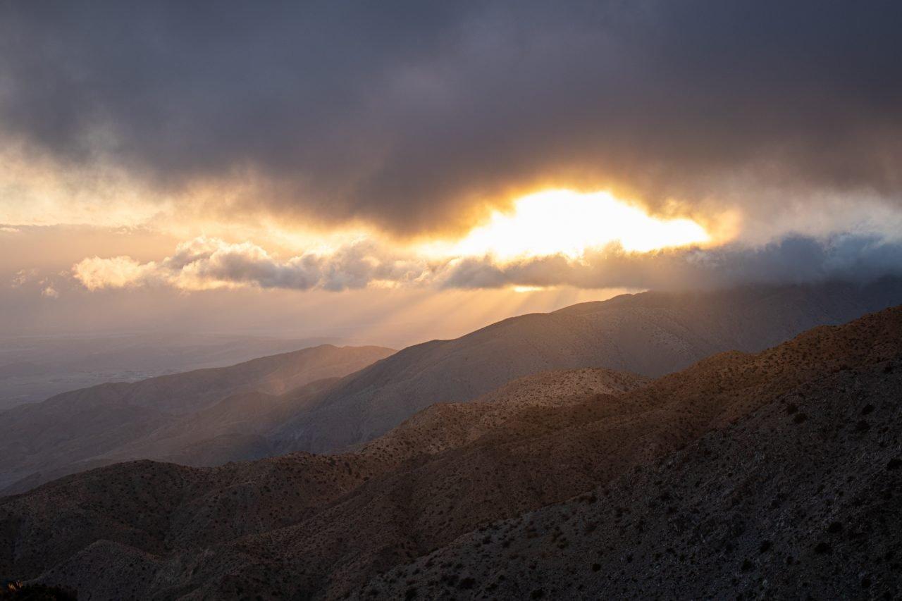 Sun Shining Through Heavy Clouds Above Hills