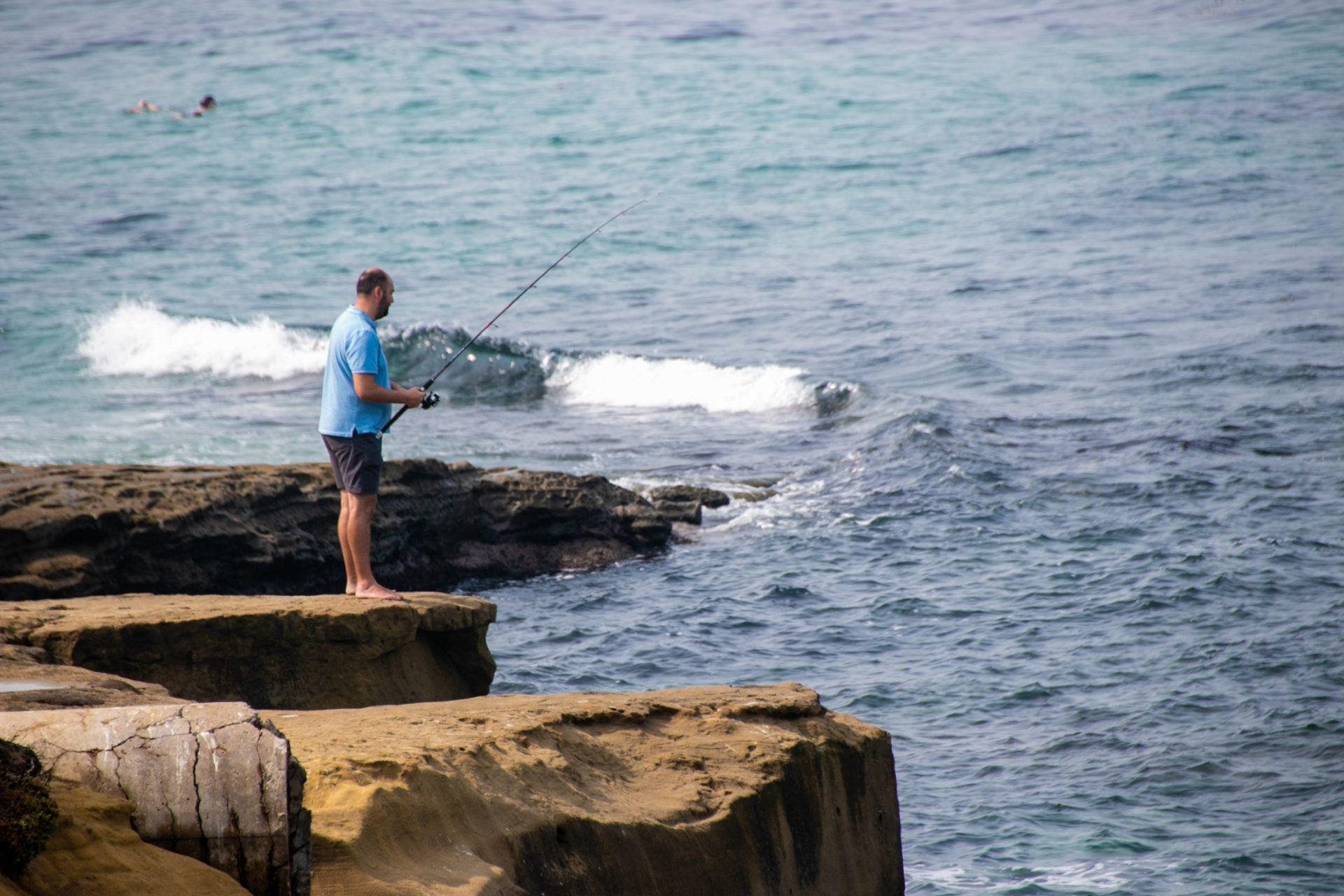Barefoot Man Fishing On Rocky Shore