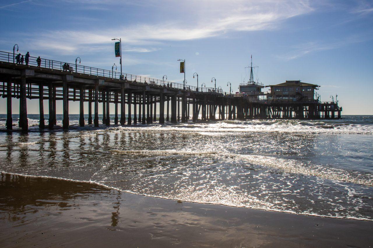 Small Twinkling Waves On Sandy Beach Near Pier