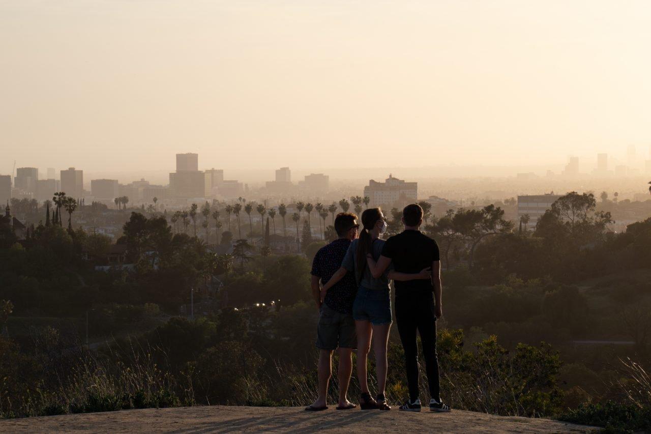 Three People Watching Sunset Beyond City Skyline