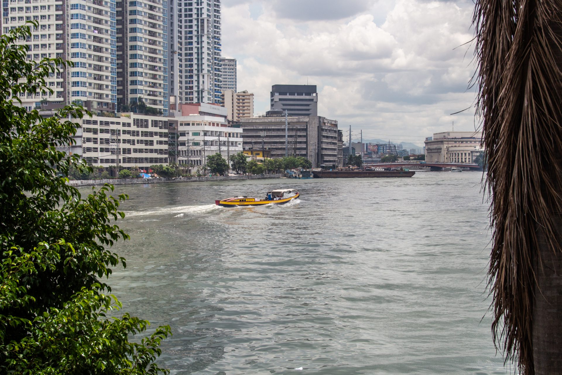 Boat Cruising Through Water Near Tall Buildings