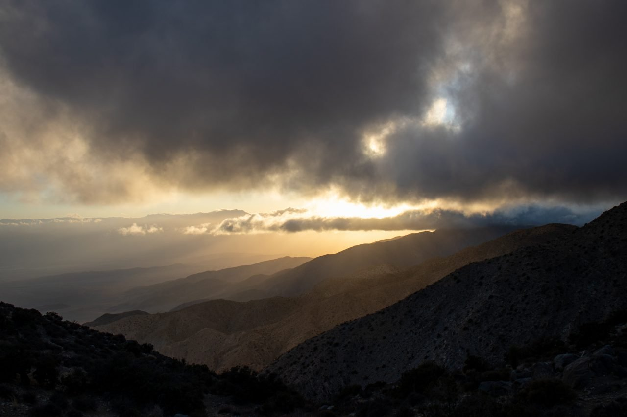 Sunset Behind Thick Clouds Above Mountains