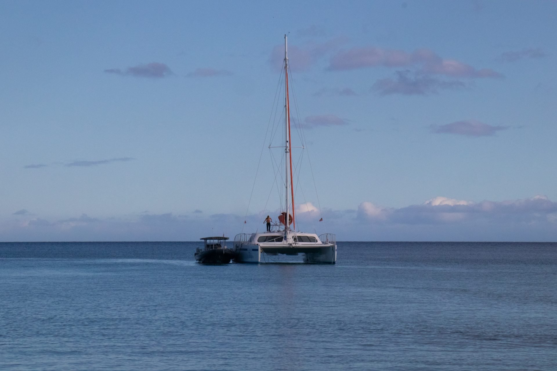 Small Boat Next To Catamaran On Water