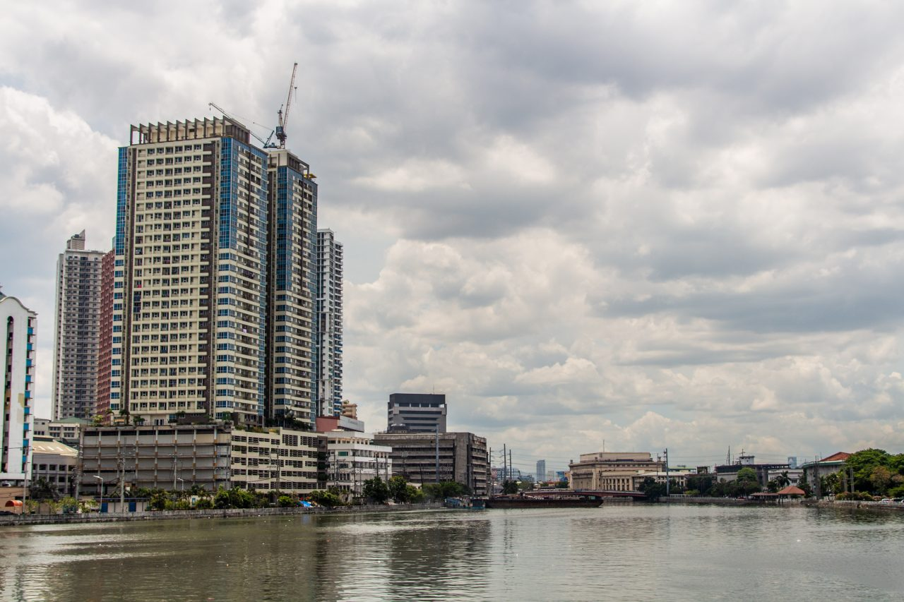 Tall Buildings On River Banks In Manila