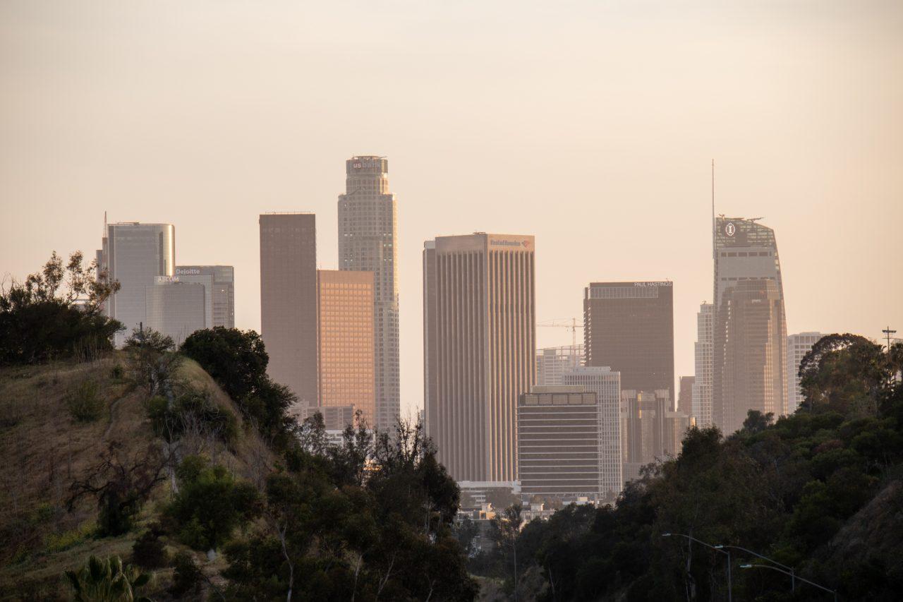Tall Buildings Through Haze Near Hills