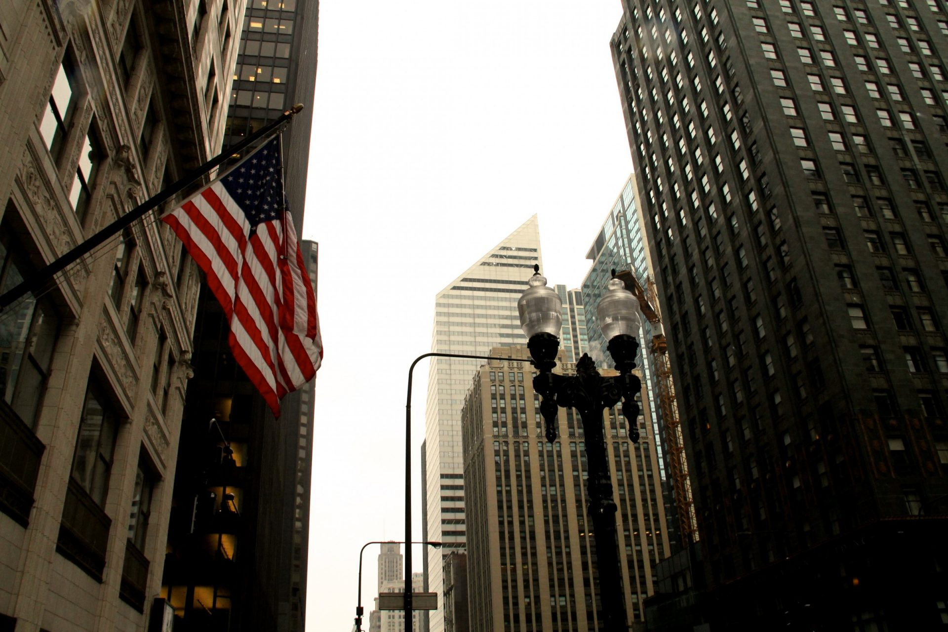 American Flag & Lamp Post Among City Buildings