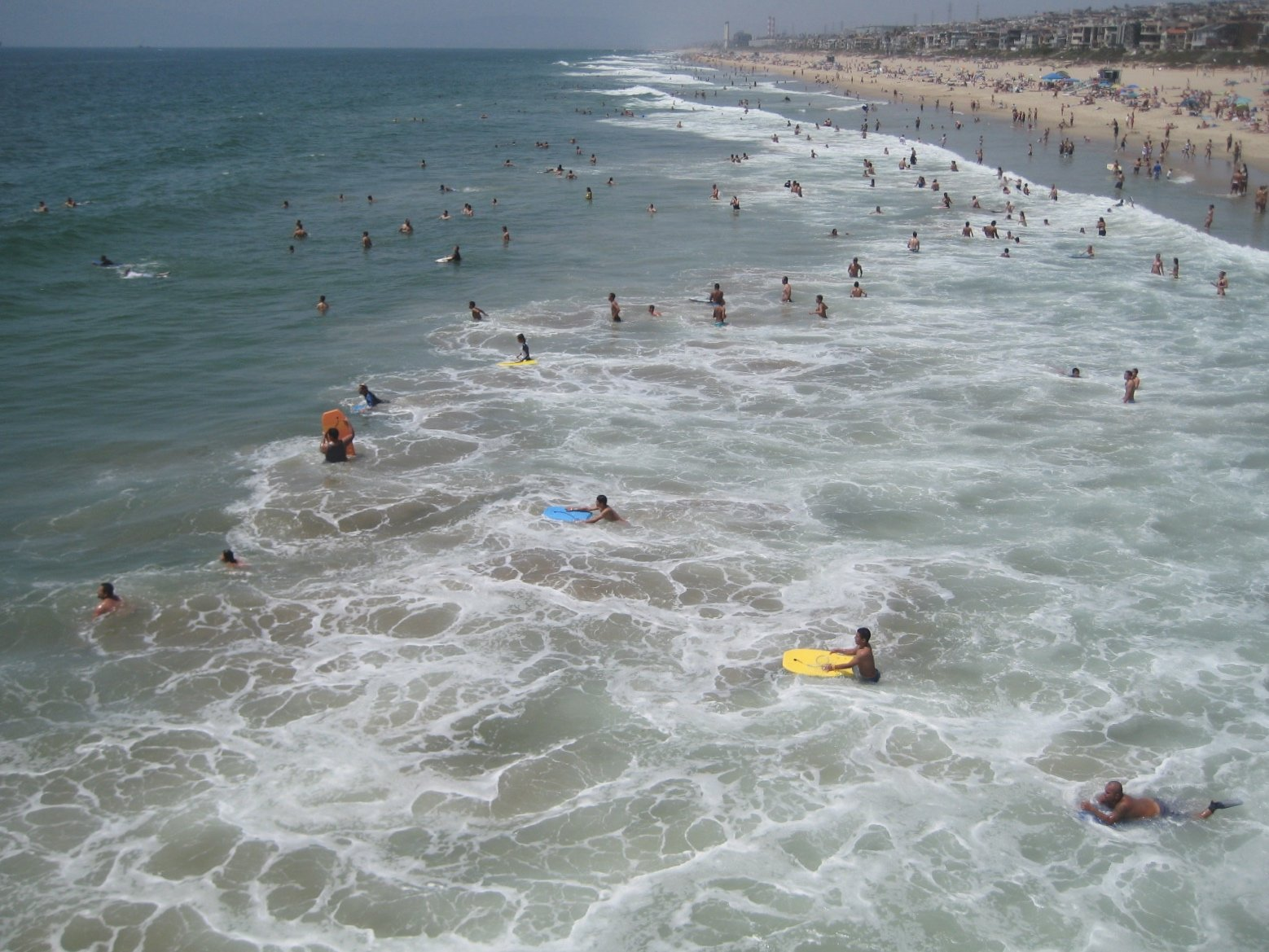 People Wading into Ocean at Beach