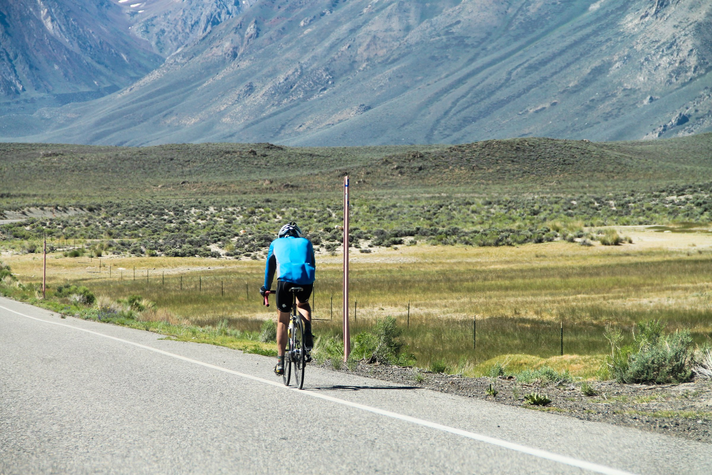 Bicyclist on Road by Fields & Mountain