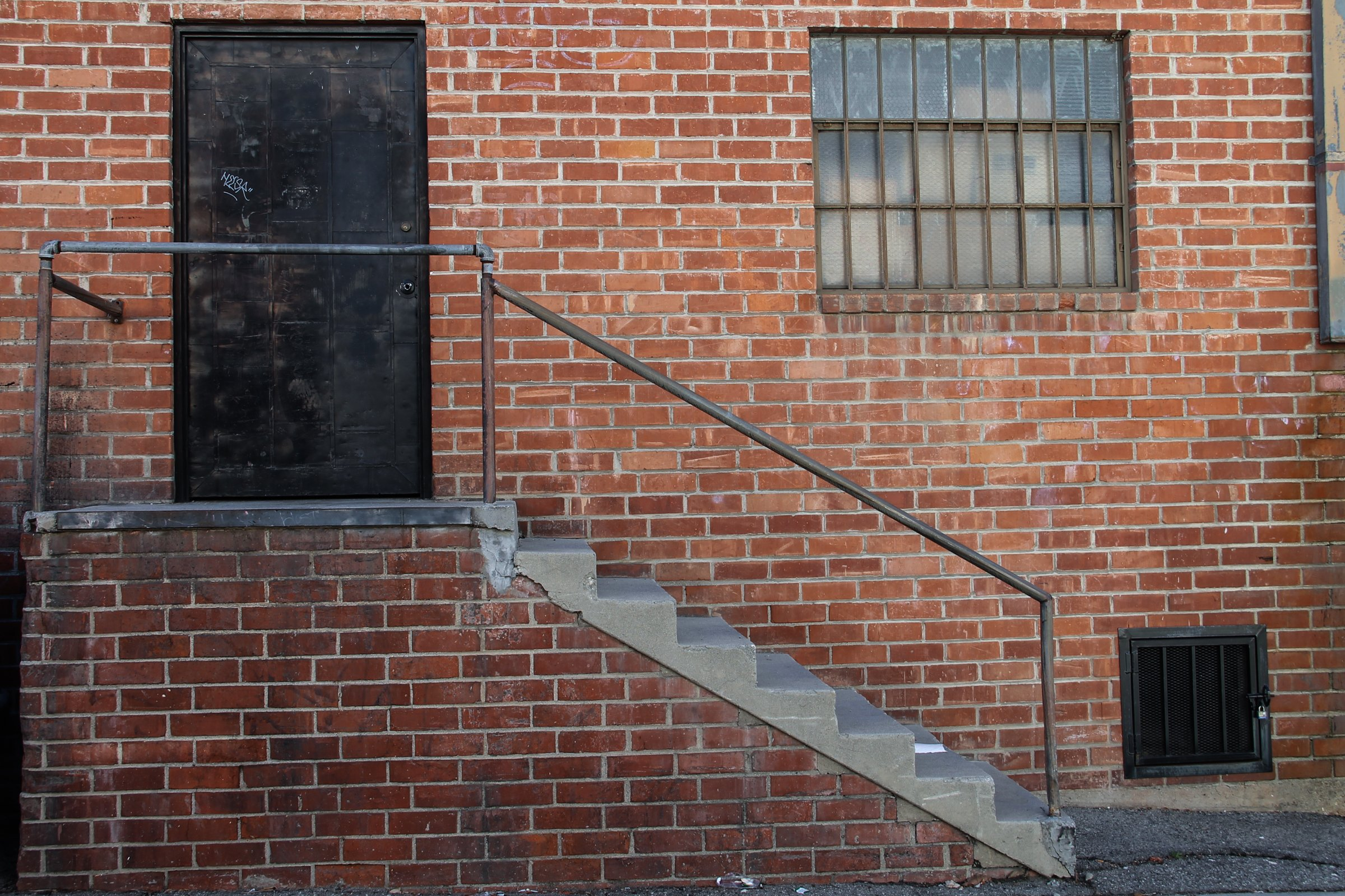 Free Stock Photo of Black Door & Staircase on Brick Building