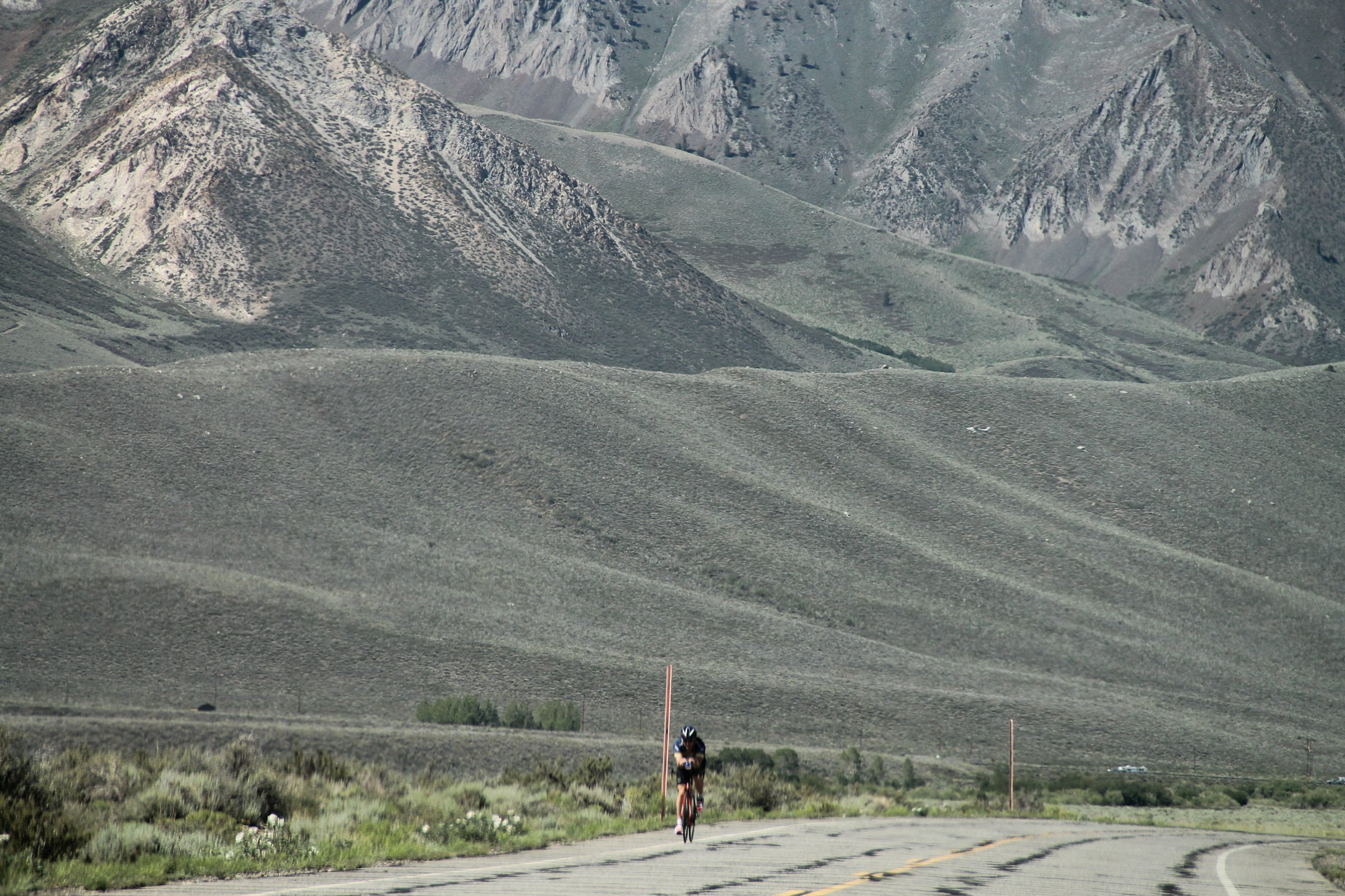 Bicyclist on Road with Mountain Behind