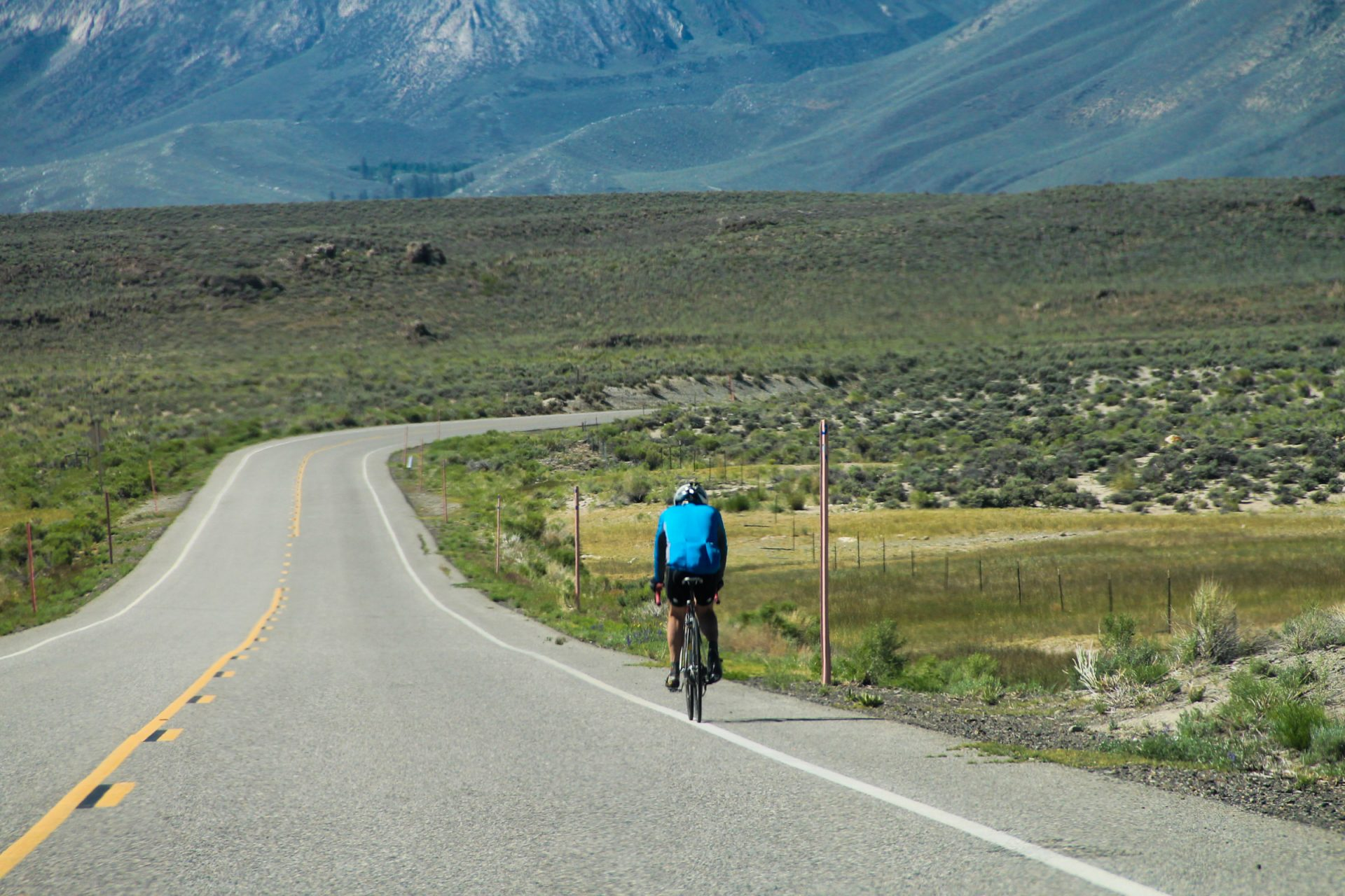 Cyclist on Road Towards Mountains