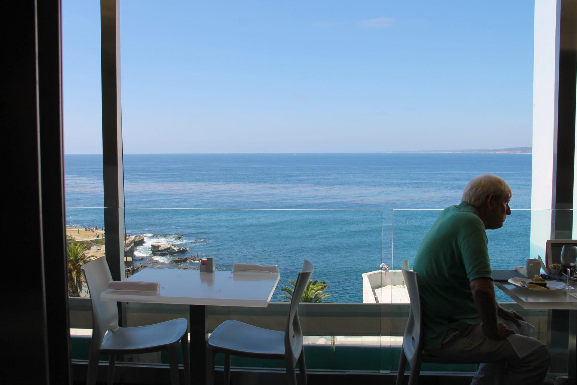 Elderly Man Sitting in Restaurant by Ocean