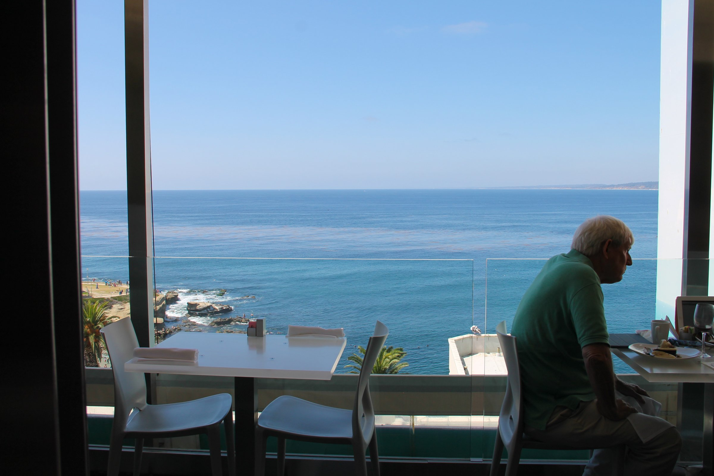 Elderly Man Sitting in Restaurant by Ocean