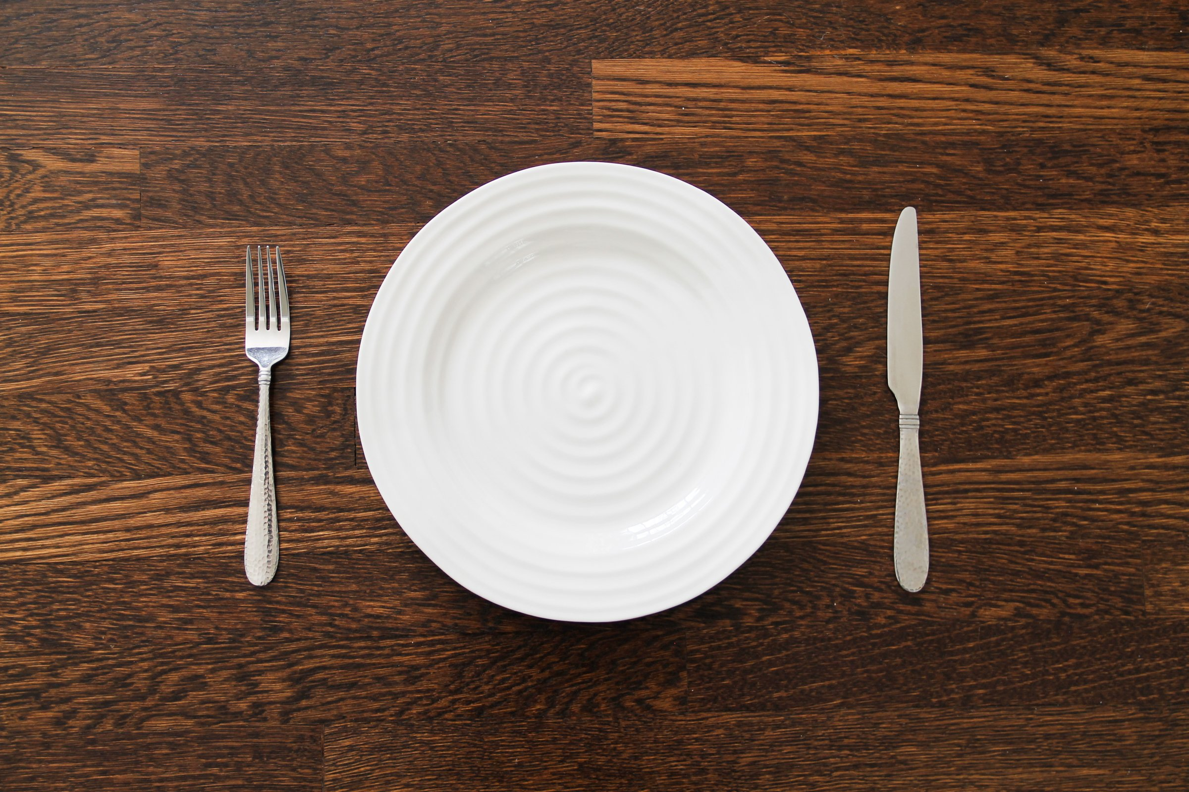 An empty white dish with knife and fork on a table - Empty Plate With Fork Knife