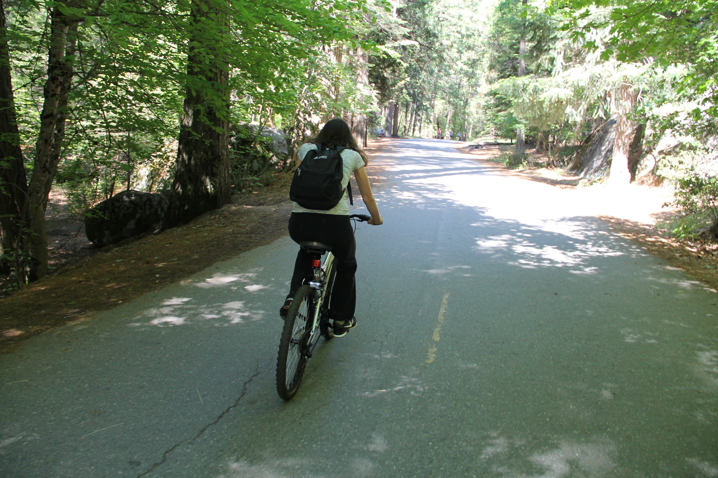 Girl Riding Bicycle on Forest Path