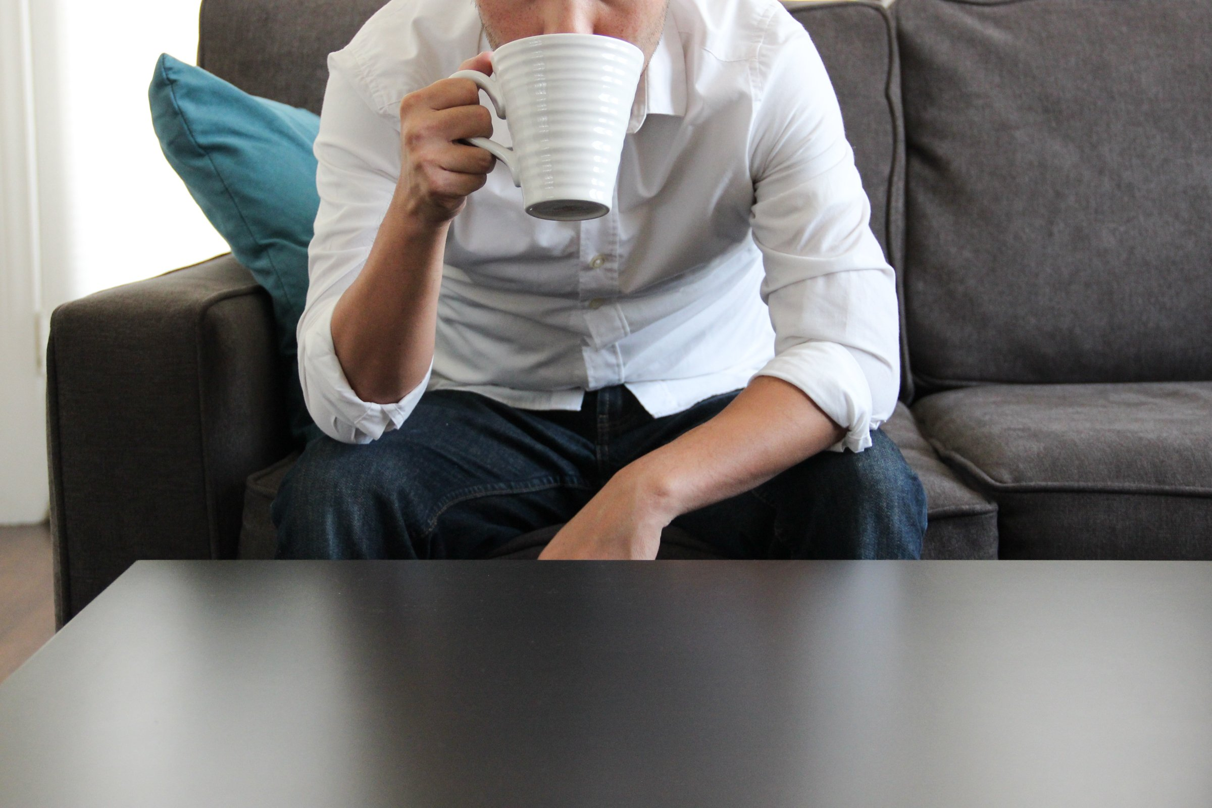 Man on Couch Drinking from Mug