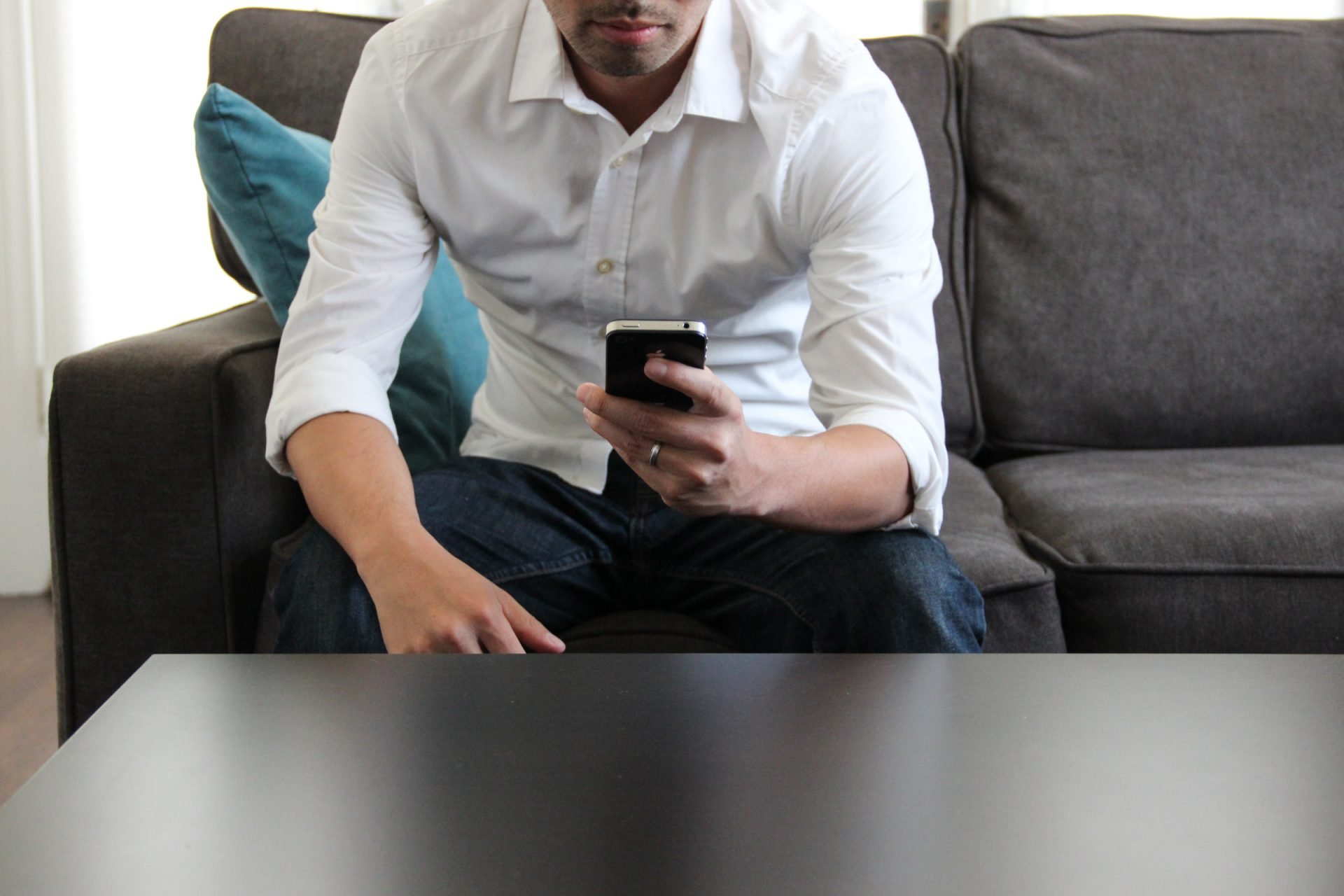 Man Sitting on Couch Using Phone