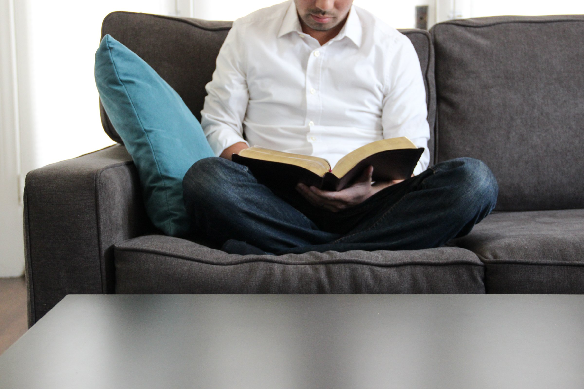 Free Stock Photo of Man on Couch Reading Bible