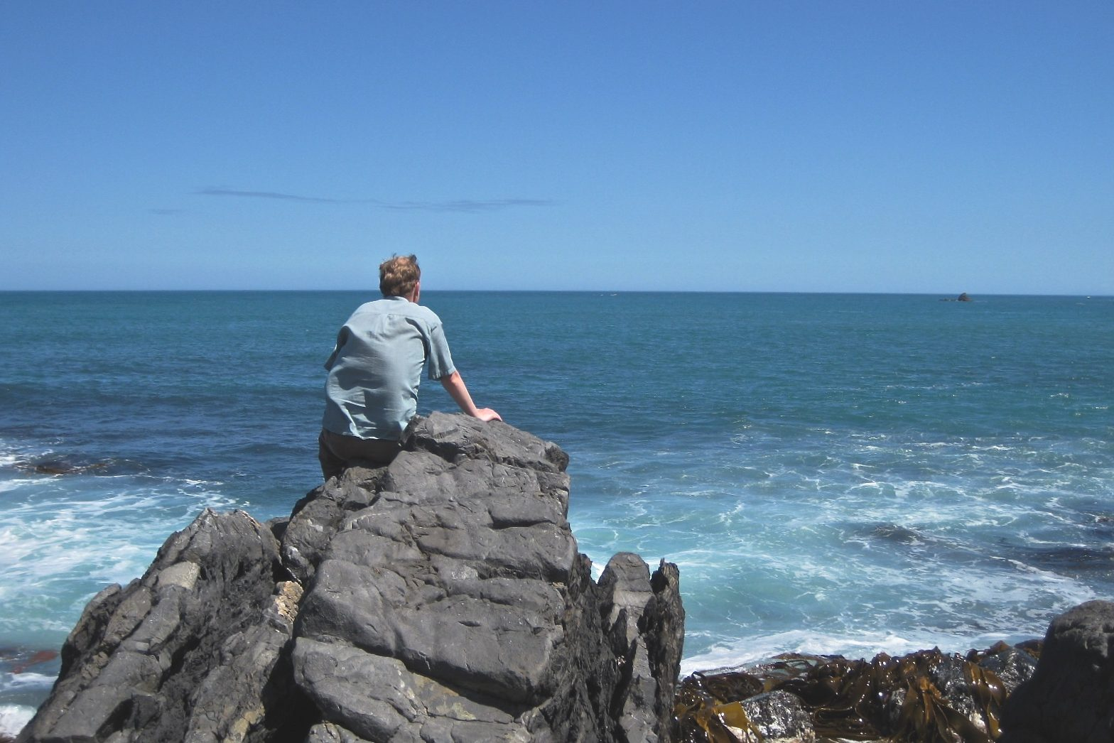 Man Sitting on Rock Looking at Ocean