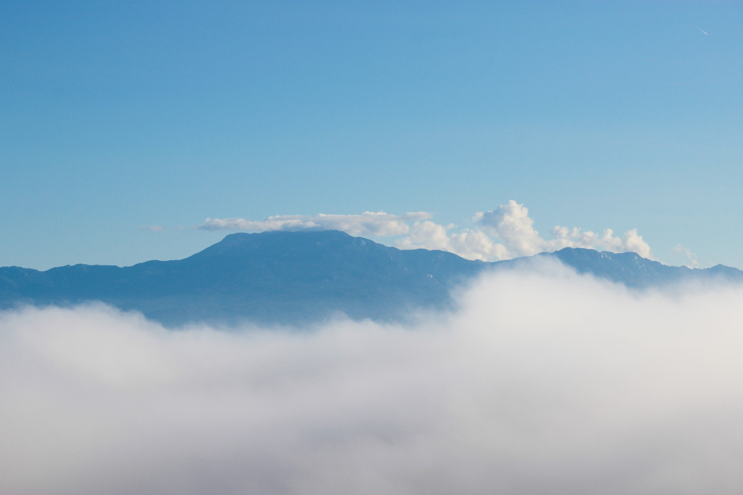 Free Stock Photo of Mountains Rising Above Clouds