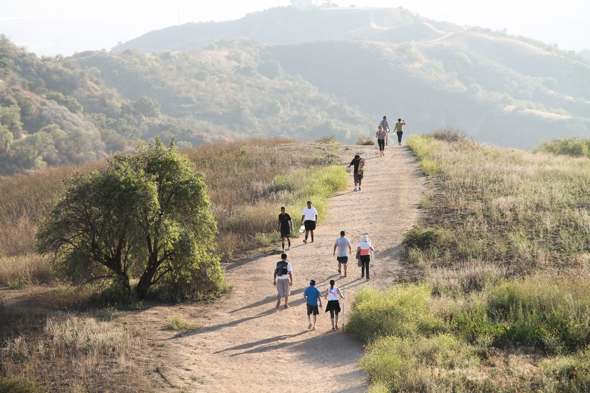 People Walking on Dry Dirt Trail Over Hill