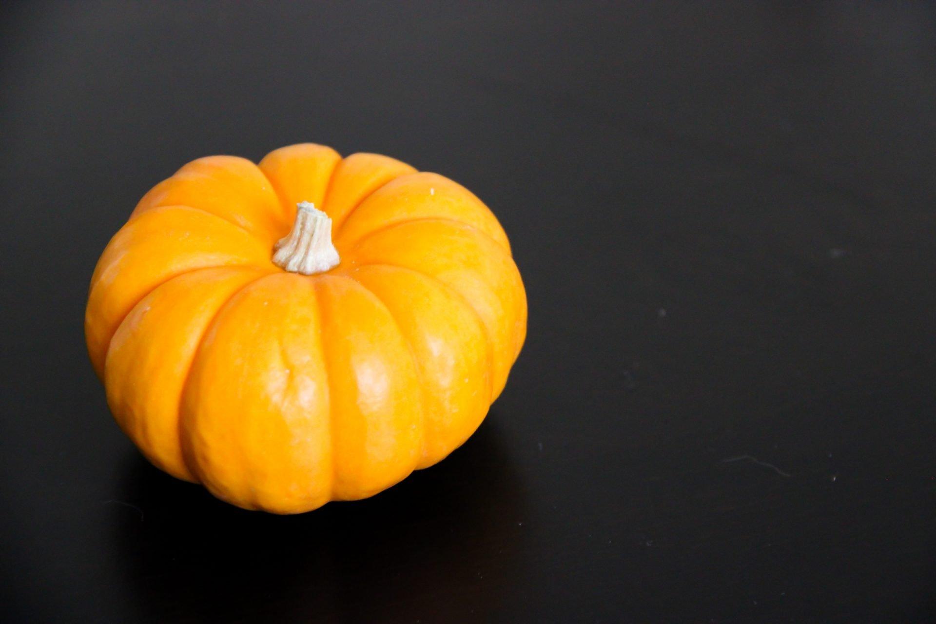 Small Orange Pumpkin on Dark Table