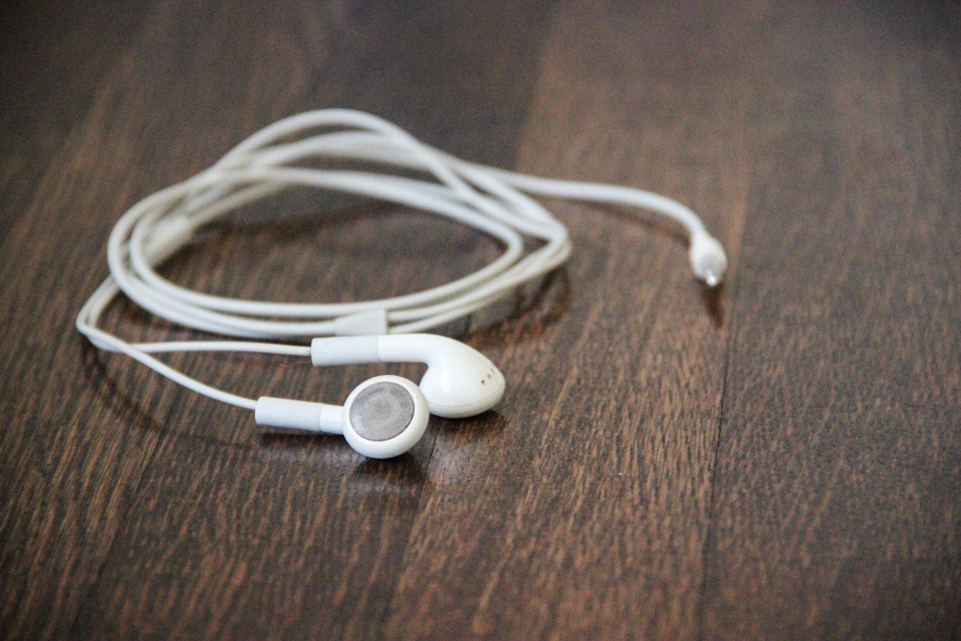 White Earphones on Wood Desk
