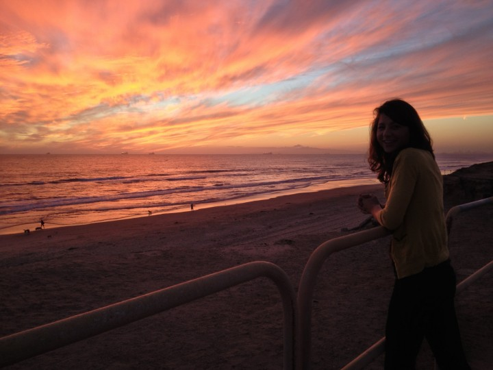 Woman Standing on Beach At Sunset