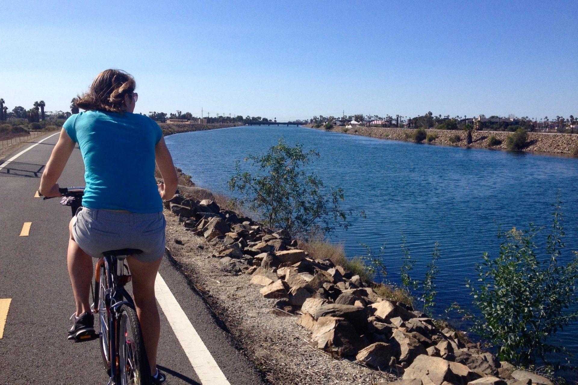 Woman Riding Bike on Path Along River